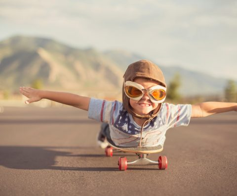 A young boy wearing flying goggles and flight cap outstretches his arms to attempt flying while he rides on his skateboard. He has a large smile across his face as he is imagining taking off.